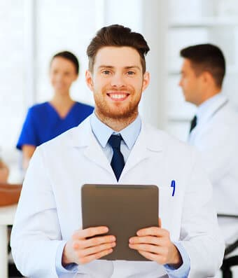 doctor smiling holding a brown notebook